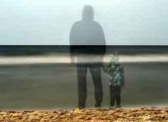 Shadow silhouettes of father and son next to ocean