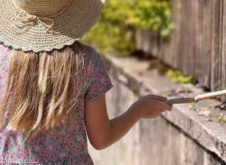 Girl wearing wide brim straw hat drags a stick along picket fence