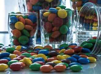 M&M Candies in cups scattered on table