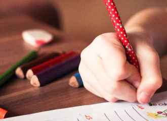 Young boy taking test with colored pencils